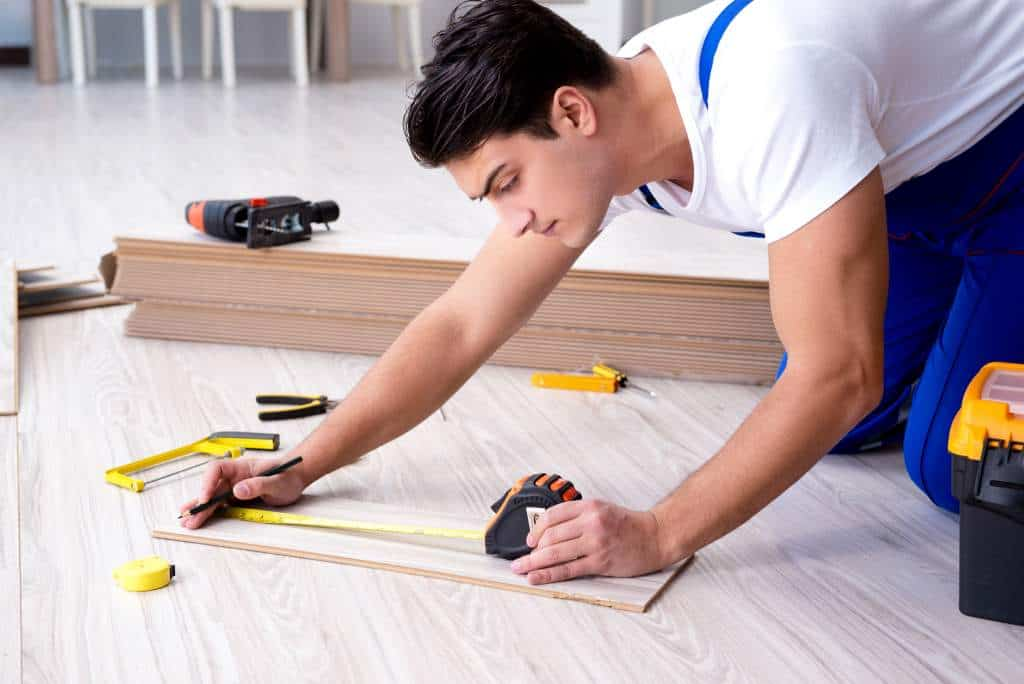 contractor laying laminate flooring home